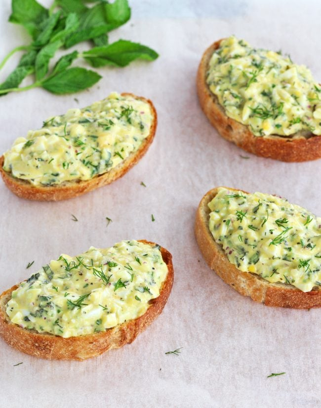 Four egg salad tartines garnished with fresh dill on top of parchment paper.
