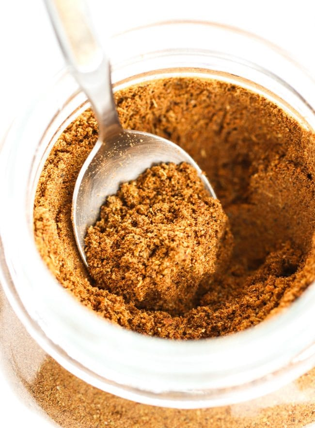 Garam Masala in a glass mason jar with a teaspoon sticking out of it from the left side.