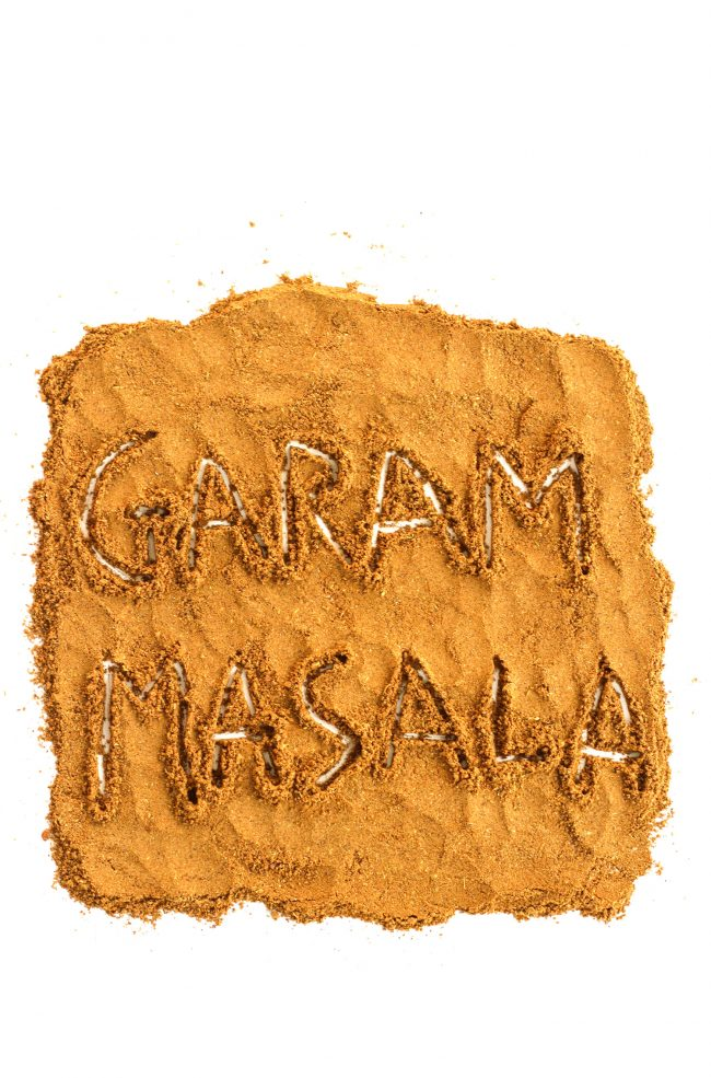 "Garam masala spread in a large square on a white background with the the letters ""G-A-R-A-M M-A-S-A-L-A"" engraved on the actual garam masala spice."