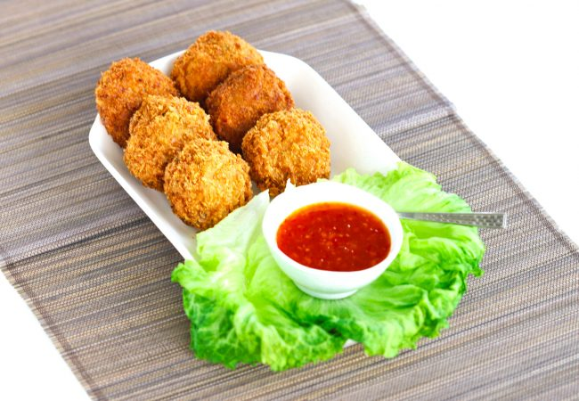 Six deep-fried Spicy Thai Shrimp Cakes on a long rectangular plate with fresh lettuce leaves and a small serving bowl with Thai Sweet Chili Sauce. There is a small teaspoon on the plate by the bowl and the rectangular plate is diagonally placed on a brown and black straw mat on top of a white background.