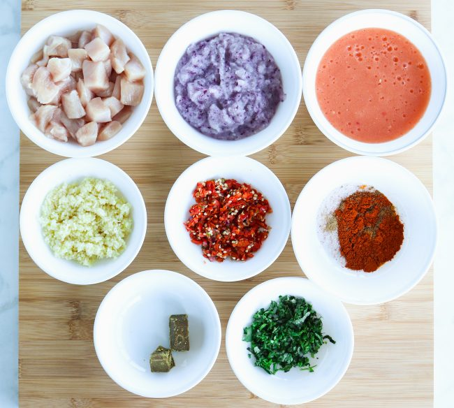 Ingredients for Indian Onion Chicken Curry displayed in small white bowls on a wooden board - diced chicken, red onion puree, tomato puree, garlic & ginger finely chopped in food processor, red & green chilies finely chopped in food processor, spice bowl with coriander powder, turmeric powder, cayenne powder, garam masala, and kosher salt, 3/4 of large cube of S&B Golden Curry roux - Extra Hot, freshly chopped coriander leaves and stems.