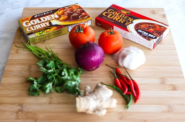 Ingredients for Indian Onion Chicken Curry displayed on a wooden board = S&B Golden Curry Roux boxes (Hot & Extra Hot), two medium tomatoes, 1 medium red onion, garlic head - unpeeled, ginger piece - unpeeled, a bunch of fresh coriander leaves, two green and five red chilies with stem.