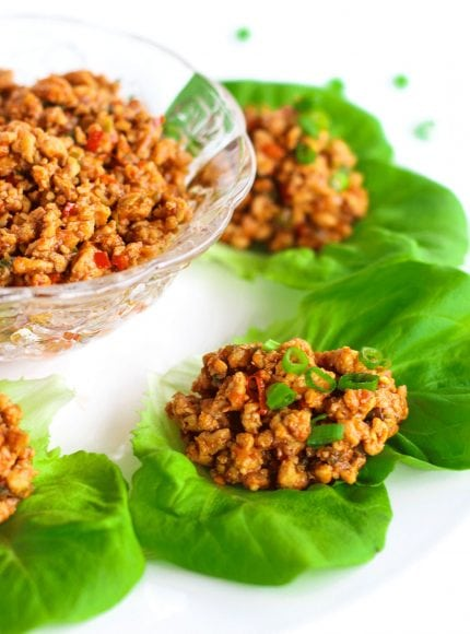 Close up photo of a Chili Chicken Lettuce Cup garnished with spring onion greens on a white round place. In the top left of photo (center of plate) is a glass serving bowl filled with chili chicken mince. Scattered spring onion greens on the white background at the top right of photo.