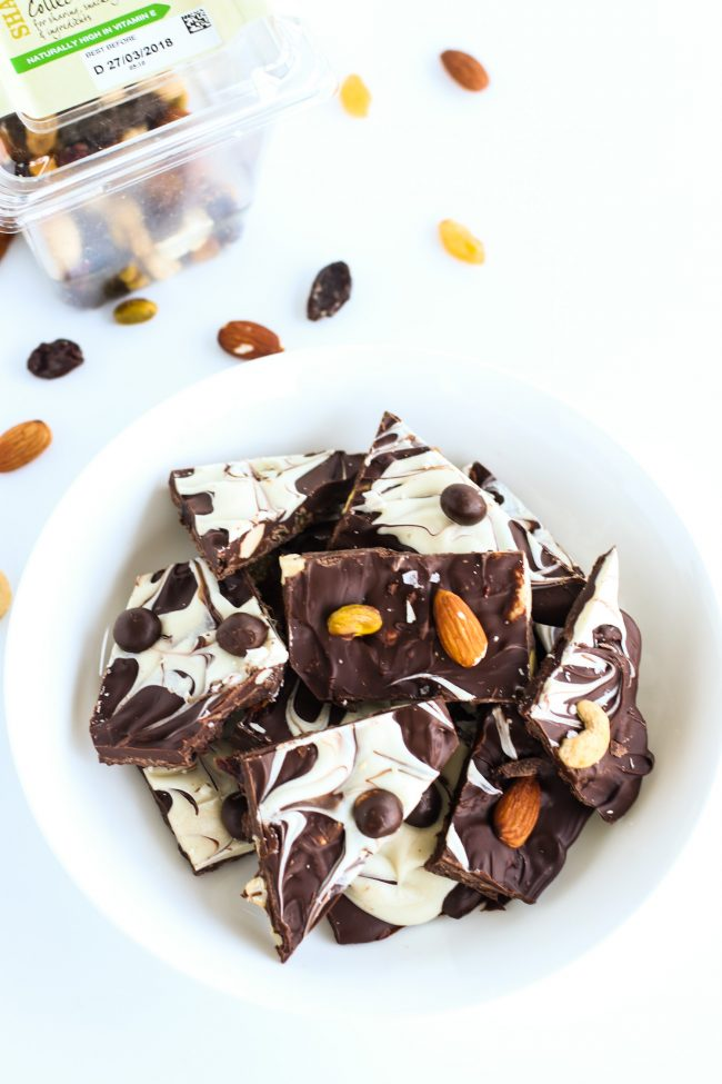 Dark and white chocolate bark pieces with mixed dried fruits and nuts and McVities Dark Chocolate Nibbles in a white bowl on a white background. Mixed dried fruits and nuts box to left back side of the photo and some scattered mixed fruits and nuts pieces on background.