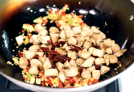 Peanuts, peppercorns, chopped red chilies, minced garlic, minced ginger, spring onion whites, 3/4 cooked chicken, and Thai dried red chilies cooking in a wok