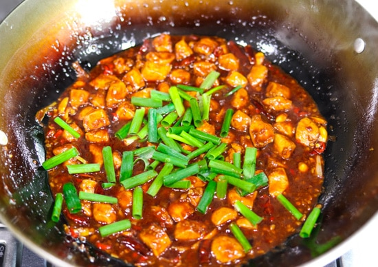 Peanuts, peppercorns, chopped red chilies, minced garlic, minced ginger, spring onion whites, diced chicken pieces and dried red chilies tossed together and simmering in spicy kung pao sauce and tossed together in a wok with spring onion greens on top of the chicken