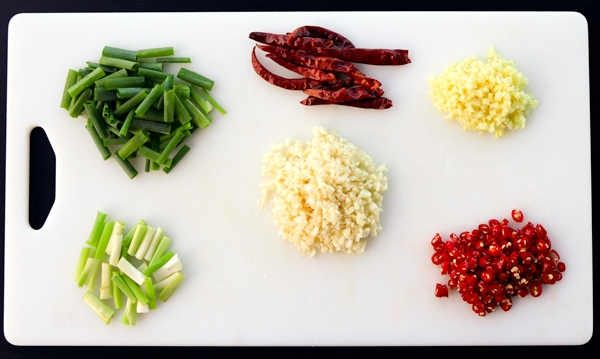 Spring onions chopped into 1 inch pieces with whites and greens separated, chopped ginger, chopped garlic, chopped fresh red chilies, and Thai dried red chilies on top of a white chopping board.