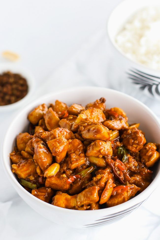 Kung Pao Chicken in a bowl over steamed white rice. Another bowl of steamed white rice and a small dish of Sichuan peppercorns to the side in the back.