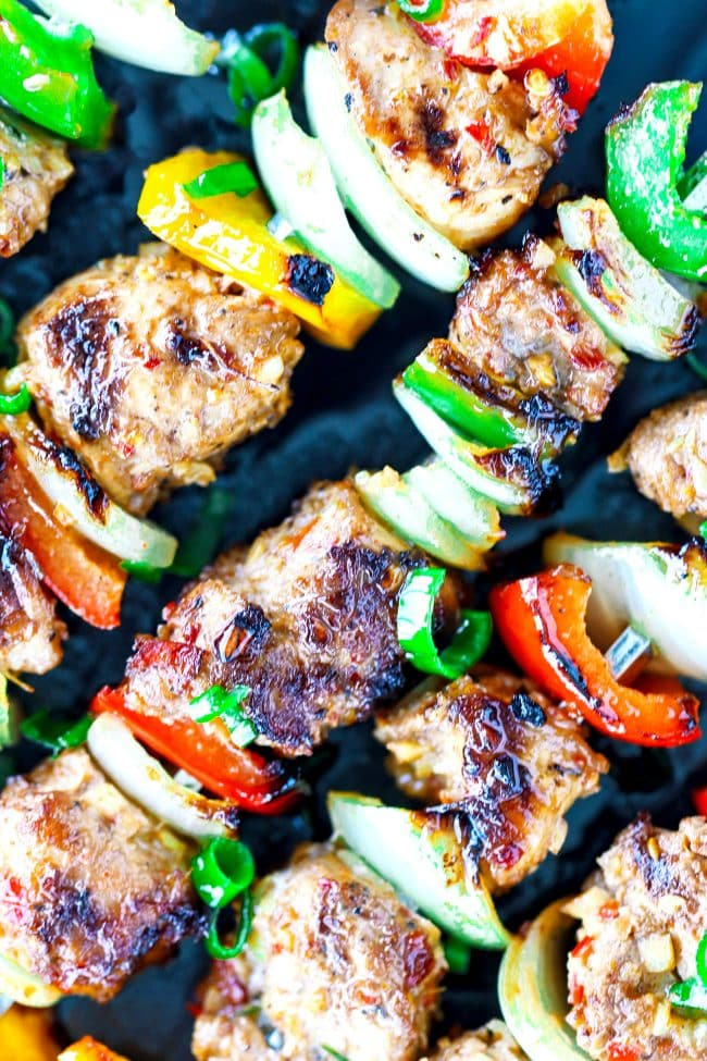 Super close up shot of Spicy Grilled Asian-Cajun Chicken Skewers diagonally placed on top of a black stone plate background. Garnished with chopped spring onion greens.