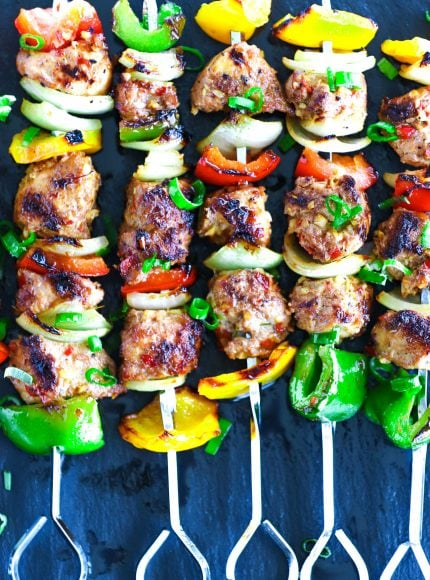 Perfectly grilled marinated chicken pieces, diced bell pepper, and diced onion threaded on metal skewers on top of a black stone plate background. Garnished with spring onion greens.