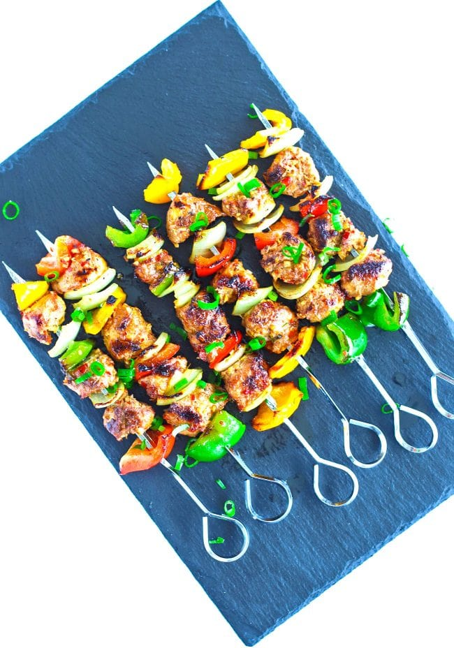 Spicy Grilled Asian-Cajun Chicken Skewers diagonally placed on top of a black stone plate background. Garnished with chopped spring onion greens.
