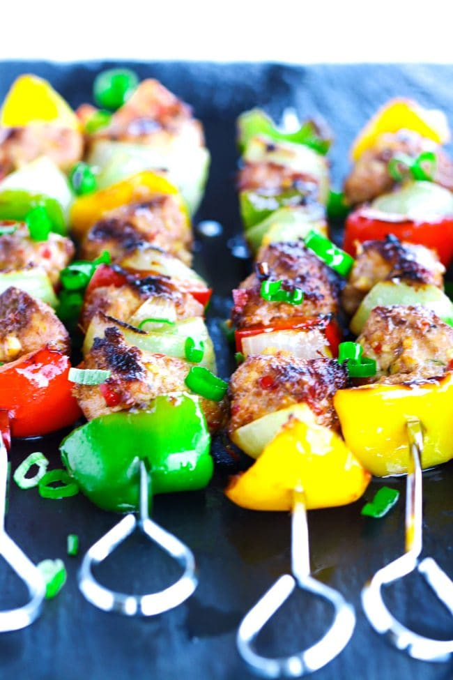 Front view of perfectly grilled Spicy Asian-Cajun Chicken Skewers on top of a black stone plate background. Garnished with chopped spring onion greens.