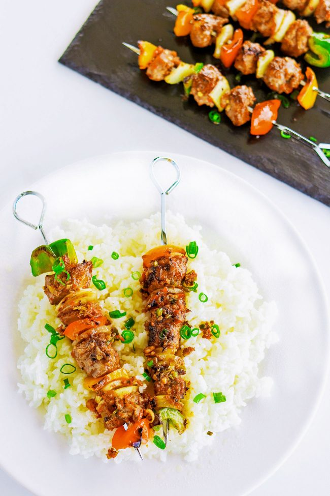 Spicy Grilled Asian-Cajun Chicken Skewers on a bed of rice in a white plate, garnished with spring onion greens. Black stone plate with more Spicy Grilled Asian-Cajun Chicken Skewers in the back.