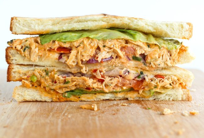 Front view of diagonally sliced Sweet & Spicy Thai Chicken Salad Sandwich stacked on top of wooden board.