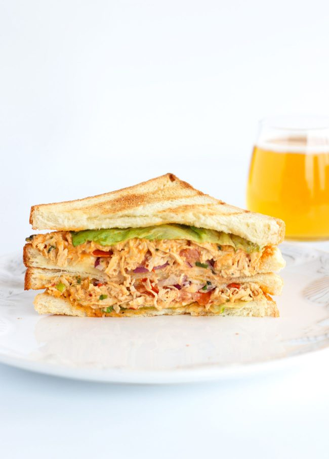 Front view of diagonally sliced Sweet & Spicy Thai Chicken Salad Sandwich stacked on top of white plate. Glass of apple juice behind the plate.