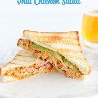 """Front view of diagonally sliced Sweet & Spicy Thai Chicken Salad Sandwich stacked on top of white plate. Glass of apple juice behind the plate. """"Sweet & Spicy Chicken Salad"""" text in baby blue above plate with sandwich."""