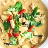 Thai Green Chicken Curry in a large deep white serving bowl on top of a round wooden chopping board. The curry is garnished with coriander, basil leaves, and red chili strips. Bowl is cut off from the photo from the left side.