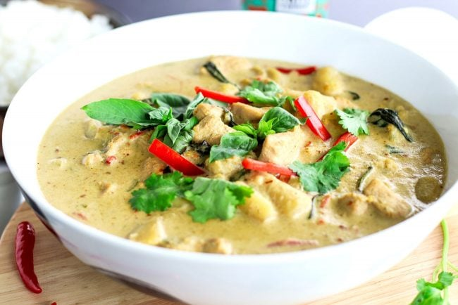 Front view of Thai Green Chicken Curry in a large deep white serving bowl on top of a round wooden chopping board which is on top of a blue striped kitchen towel. The curry is garnished with coriander, basil leaves, and red chili strips. Bowl of steamed white rice and white soup ladle to the side. Bottle of ice cold beer in the back.