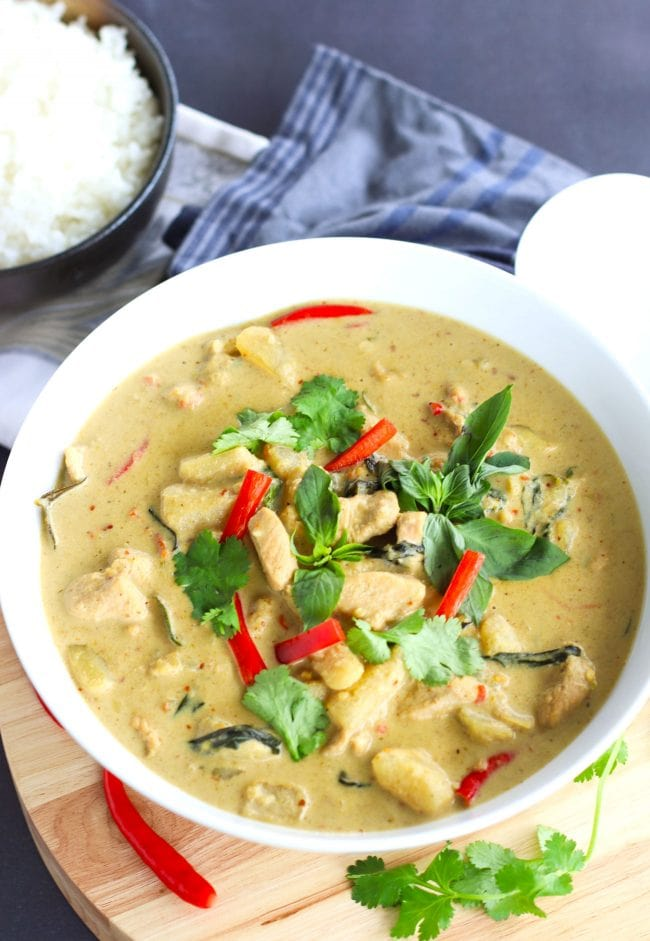 Thai Green Chicken Curry in a large deep white serving bowl on top of a round wooden chopping board which is on top of a blue striped kitchen towel. The curry is garnished with coriander, basil leaves, and red chili strips. Bowl of steamed white rice on a folded white napkin and white soup ladle to the side. Backdrop color is black chalkboard.