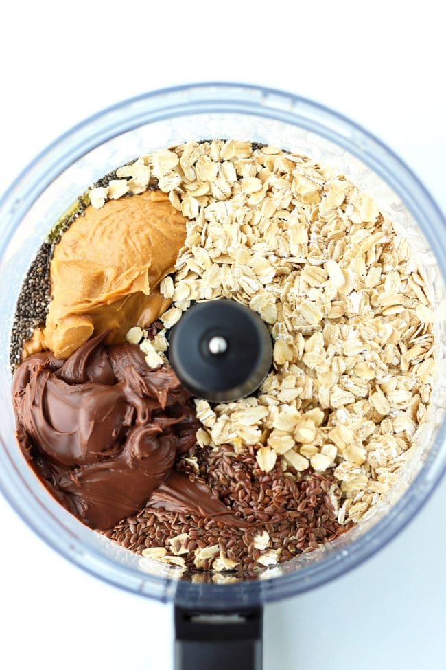 Food processor bowl with ingredients for Nutella & Peanut Butter Energy Balls: old fashioned rolled oats, chia seeds, flax seeds, peanut butter, Nutella, kosher salt, almond extract, and honey.