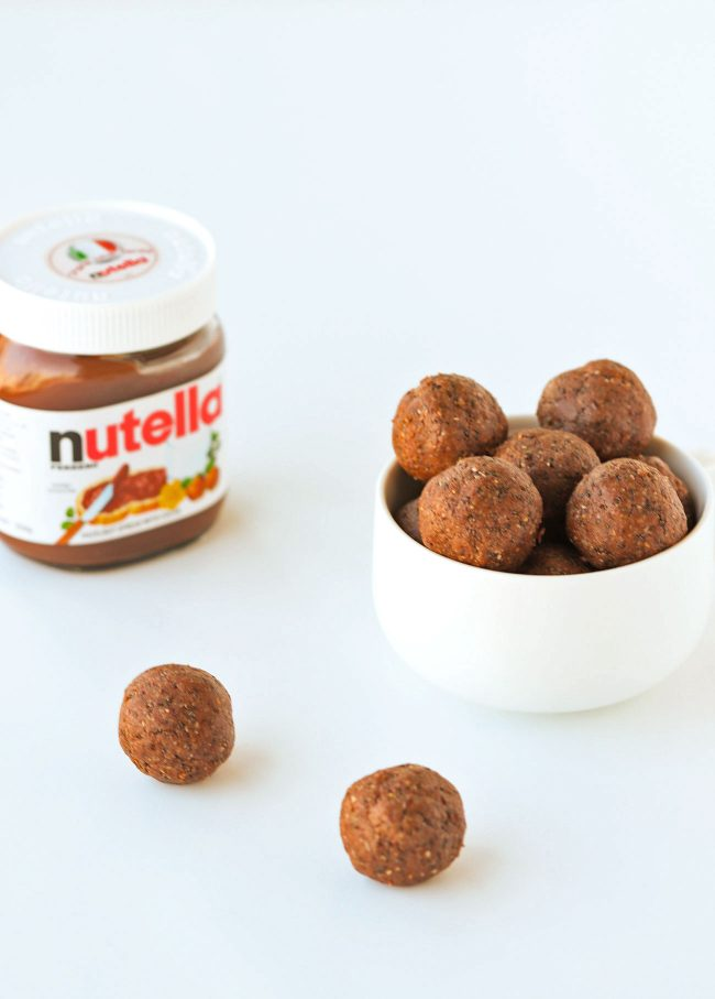 White bowl of Nutella & Peanut Butter Energy Balls stacked high with two balls in front of the bowl on a white backdrop. Jar of Nutella on the left side of the bowl.