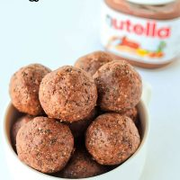 White bowl of Nutella & Peanut Butter Energy Balls stacked high with two balls in front of the bowl on a white backdrop. Jar of Nutella on the back right side of the bowl.