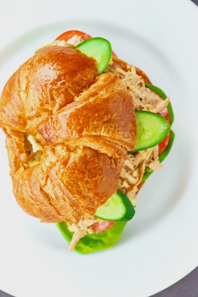 Overhead close up view of Spicy Asian-Cajun Chicken Salad Croissandwich on a white plate on top of a chalkboard backdrop.