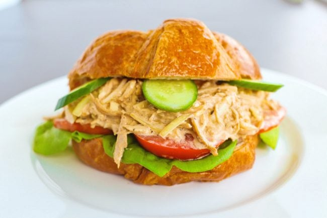 Front view of a Spicy Asian-Cajun Chicken Salad Croissandwich on a white plate on top of a chalkboard backdrop.