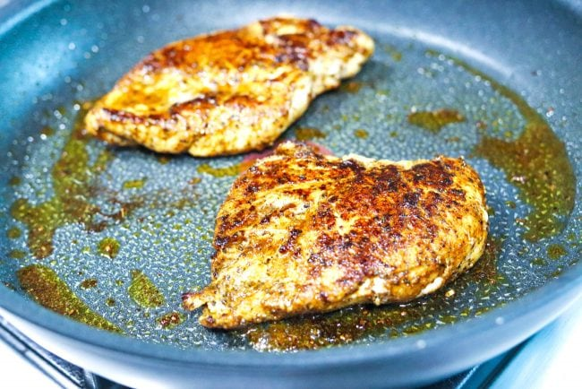 Two pan-seared Cajun spiced chicken breasts in a black pan on the stovetop.