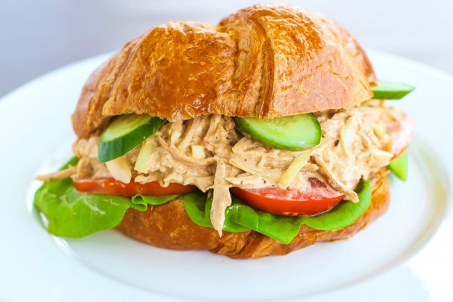 Spicy Asian-Cajun Chicken Salad Croissandwich made with tomatoes, butter lettuce, cucumber slices on top of a white plate on a chalkboard backdrop.
