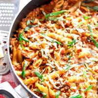 Spicy Chicken Penne Pasta in a large black pan on top of a checkered red and white napkin and garnished with freshly chopped basil leaves and Parmigiano Reggiano cheese. To the left side of the pan is a silver cheese grater with a small block of cheese on top.