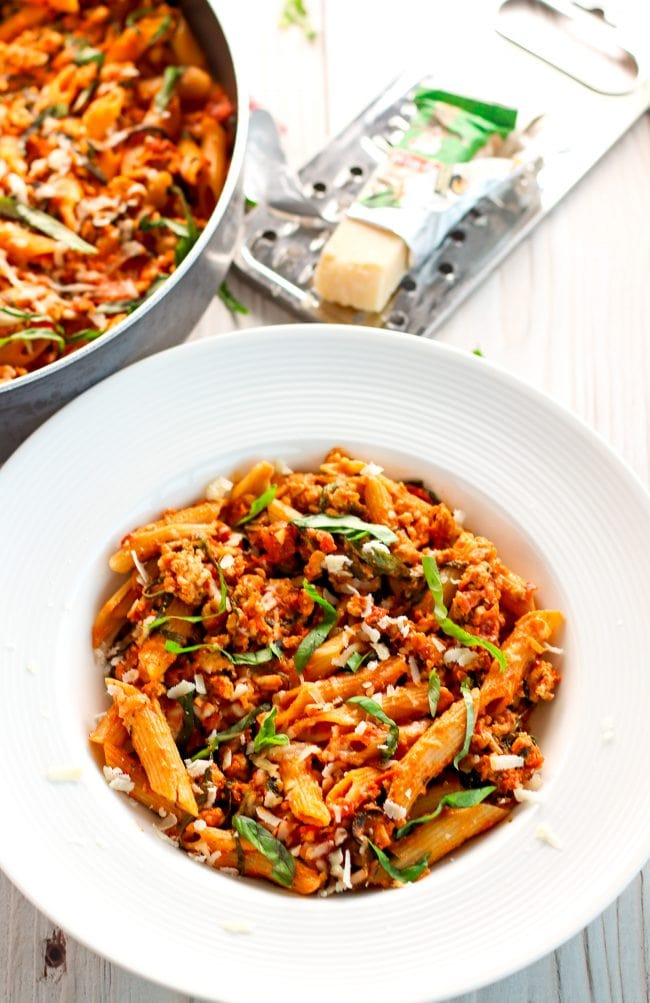 Spicy Chicken Penne Pasta in a large black pan on top of a checkered red and white napkin on a light wood backdrop. The pan of pasta is garnished with freshly chopped basil leaves and Parmigiano Reggiano cheese. To the top right side of the pan is a silver cheese grater with a block of cheese in its packet on top. Below in the center is a deep white plate with Spicy Chicken Penne Pasta that is garnished with basil and freshly grated cheese. Some chopped basil leaves is scattered on top of the wooden table backdrop.