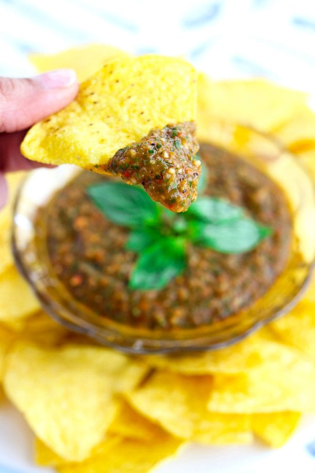 Fingers holding up a tortilla chip that has been dipped into Thai Sweet Basil Roasted Tomato Salsa above a glass bowl with the salsa that is surrounded by tortilla chips on a white plate.