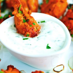 A chicken tikka drumette in a dipped into a small dish of cucumber and mint yogurt dip surrounded by chicken tikka drumettes on a white plate.