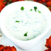 Cooling Cucumber & Mint Yogurt Dip in a white pear shaped serving bowl, garnished with fresh coriander leaves.