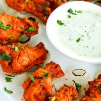 Close up of left side of square plate loaded with oven grilled chicken tikka drumettes and a small dish of cucumber and mint yogurt dip in the center of the plate.