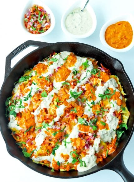 Overhead view of cast iron skillet of Chicken Tikka Nachos with Creamy Cooling Yogurt Sauce and Red Chili sauce drizzled over the top. Garnished with freshly chopped coriander. Above the skillet are three dip bowls filled with pico de gallo, creamy cooling yogurt sauce, and a red chili sauce.