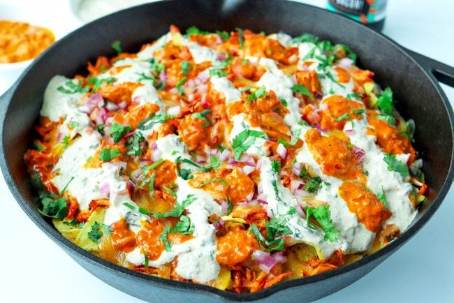 Front close up view of cast iron skillet with Chicken Tikka Nachos, topped with Creamy Cooling Yogurt Sauce and Red Chili sauce drizzled over the top. Garnished with freshly chopped coriander.
