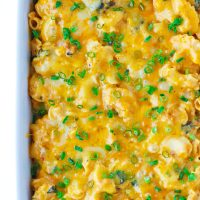Overhead view of Creamy Buffalo Sauce Bacon Mac and Cheese, fully baked and garnished with chopped spring onion greens, in a 9x13 white baking dish. Right side of dish cut off from photo.