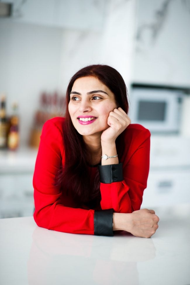 Picture of Lavina from That Spicy Chick leaning on top of a marble island in a kitchen
