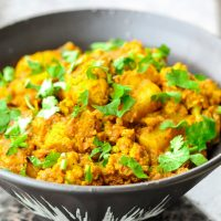 Cauliflower and potato dry curry in a black bowl and garnished with chopped coriander. Bowl is on top of a brown marble window ledge.