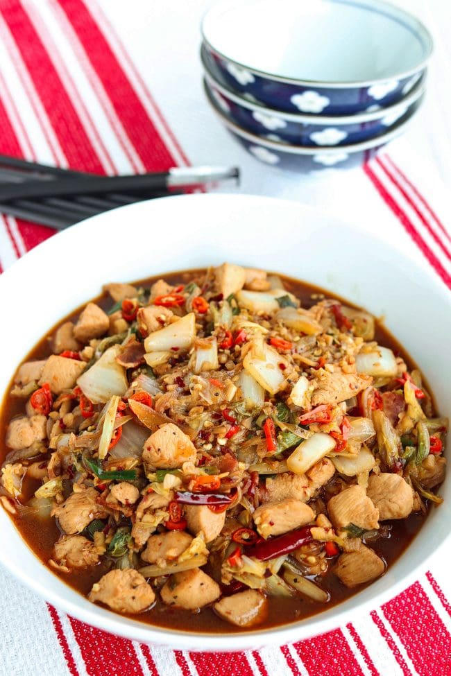 round white serving bowl with stir-fried chicken, bacon, cabbage, and dried red chillies in sauce . Chopsticks and stacked bowls in the back.
