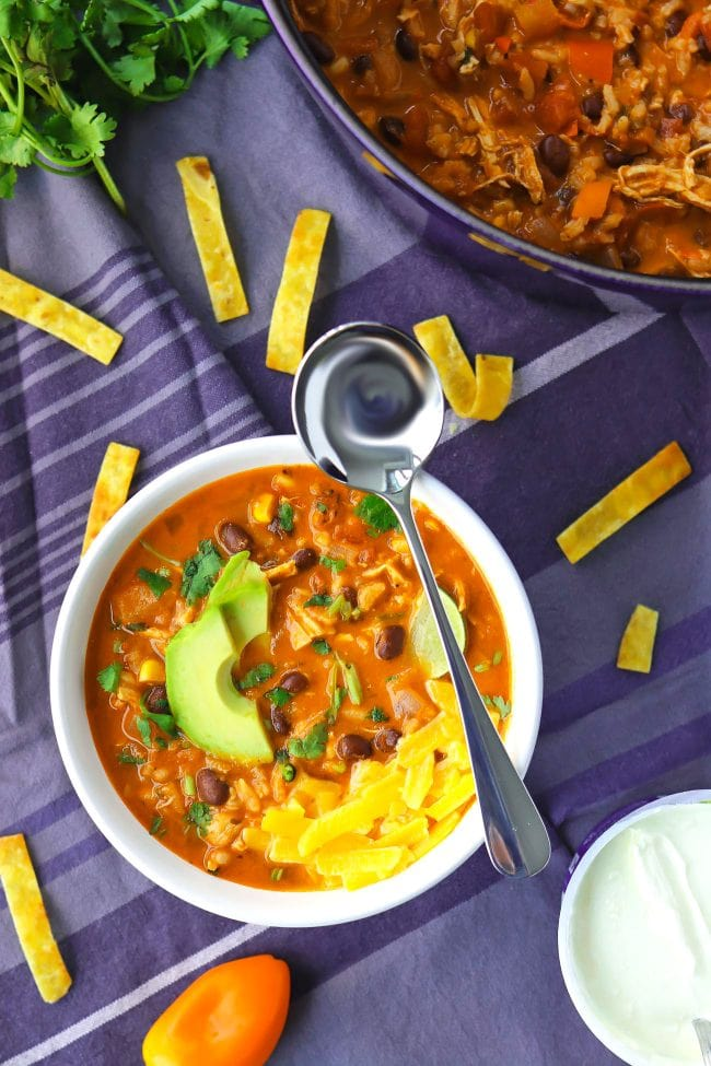 Bowl of Mexican Chicken Tortilla Soup with spoon and toppings. Pot of soup, coriander sprigs, sweet peppers, and sour cream in a carton surrounding the the bowl.