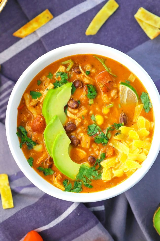 Bowl of Mexican chicken soup topped with corn, black beans, avocado slices, cheese, and a lime slice, with tortilla chips around the bowl