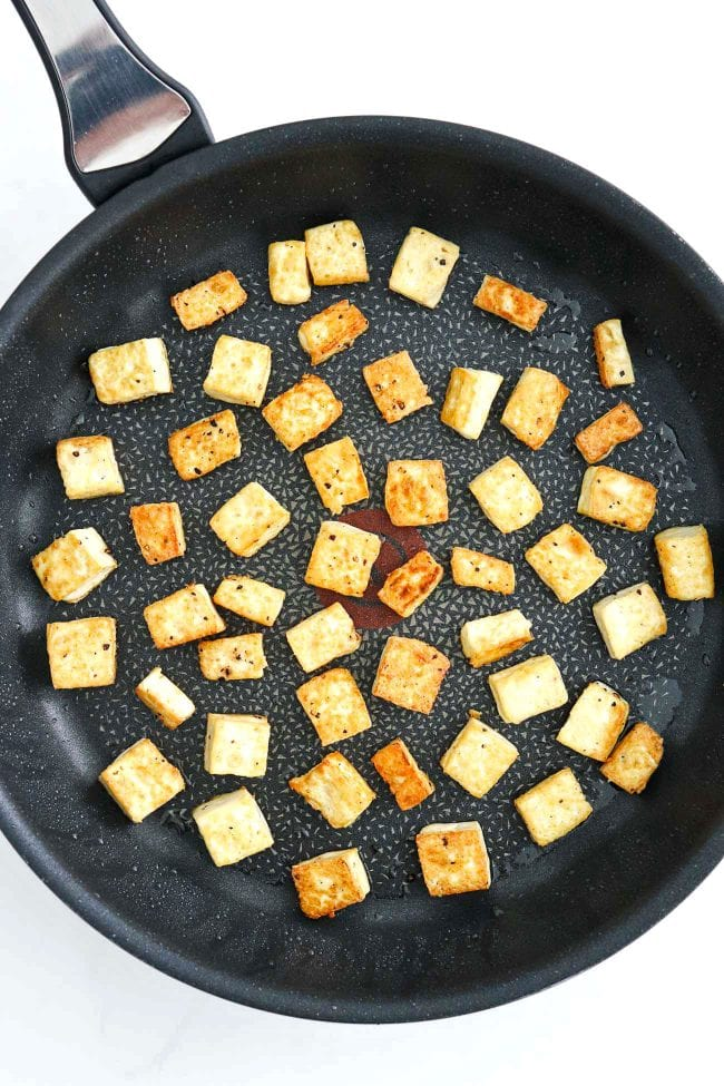 Nonstick black skillet with pan-fried tofu cubes