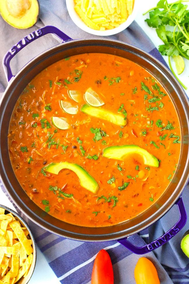 Pot of red soup surrounded by bowl of tortilla chips, cheddar cheese, avocado, coriander springs, and lime slices