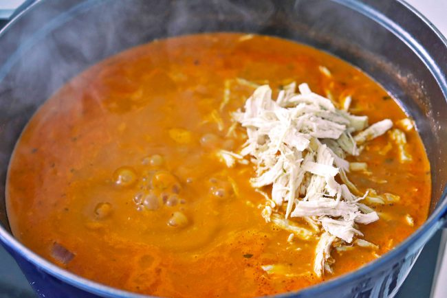 Shredded chicken being added to pot of bubbling soup on the stovetop