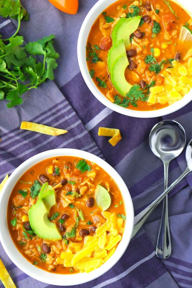 Two bowls of creamy Mexican soup with toppings - avocado slices, coriander, and cheese. Spoons and scattered tortilla chips on the side on top of a blue background