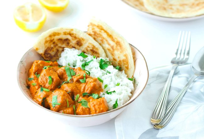 bowl with rice, roti paratha, and paneer in butter tomato cream curry. spoon and fork on napkin next to bowl.