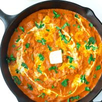paneer butter masala garnished with cream, unsalted butter and coriander in cast iron skillet